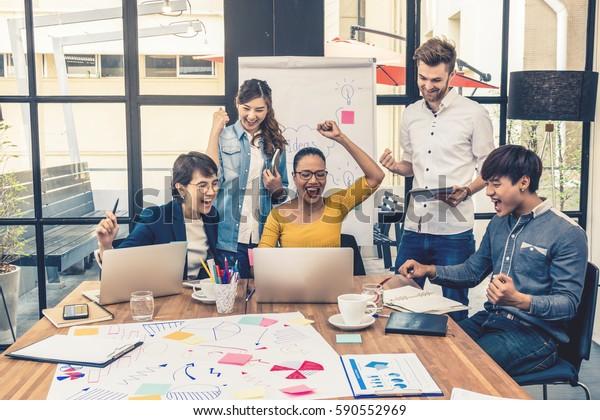 Grupo de empresarios asiáticos y multiétnicos con traje informal trabajando con acción feliz y celebrar en la Oficina moderna, el concepto de grupo empresarial de personas
