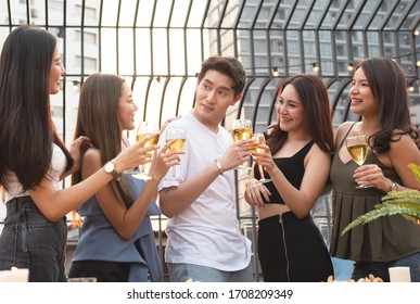 Group of asian multiple gender holding glass of wine chat together with friends while celebrating dance party on outdoor rooftop nightclub,leisure lifestyle of young friendship enjoyment concept.