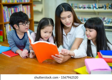 A Group of Asian Student Kid Reading a book with women teacher in School library with Shelf of Books in Background, Asian Kid Education Concept