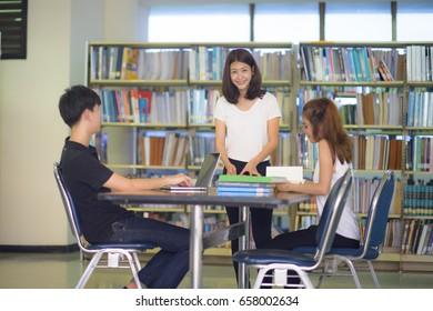 group of asian student reading and working research in library of University