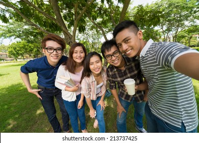 Group of Asian students taking selfie in the park