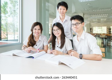 Group of asian students in uniform studying together at classroom