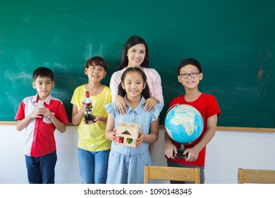 Group of Asian students with woman teacher standing on chalkboard and holding stationary with smiling feel good