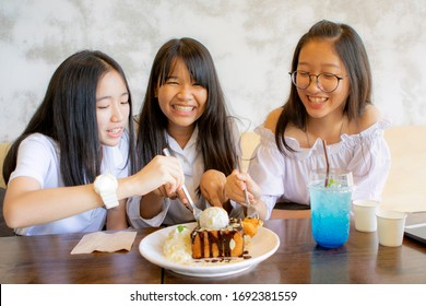 group of asian teenager eating icecram toast in  home living room