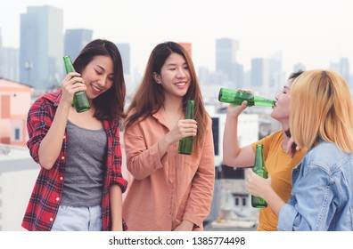 Group of asian women drinking at rooftop party, outdoors celebration