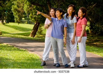 A group of Asian women standing together in the park looking at something of interest