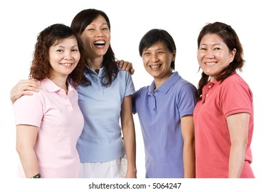 A group of Asian women standing together in the studio talking