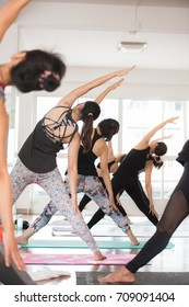 Group Asian women stretching and practices yoga in a class, healthy lifestyle and fitness concept. Selective focus. - Shutterstock ID 709091404