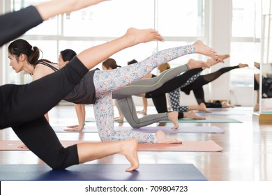 Group Asian women stretching and practices yoga in a class, healthy lifestyle and fitness concept. Selective focus. - Shutterstock ID 709804723