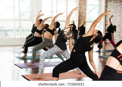 Group Asian women stretching and practices yoga in a class, healthy lifestyle and fitness concept. Selective focus and background blurred.  - Shutterstock ID 711824311