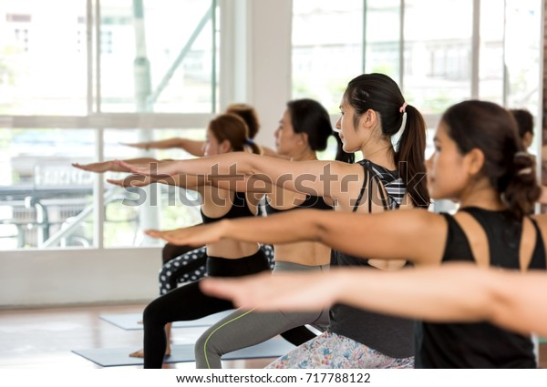 Group Asian women stretching and practices yoga in Warrior pose in a class, healthy lifestyle and fitness concept. Selective focus
