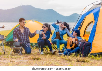 Group of Asian young sitting drinking coffee and playing guitar to happily near lake and the tent camp on outdoors camping. Lifestyle and camping concept.