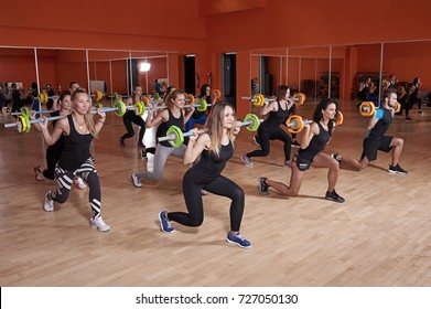 Group of athlete doing fitness training exercise, lunge with barbell in the gym.  Functional training, cross fit, gym and lifestyle concept.