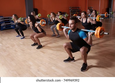 Group of athlete doing fitness training exercise, lunge with barbell in the gym.  Functional training, crossfit, gym and lifestyle concept.