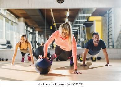 Group of athletes doing push ups at gym.