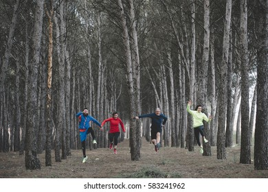 Group of athletes jumping in the forest.