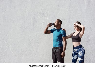 Group of athletes relaxing on the wall background and resting after hard street workout session. Man, woman and urban sport