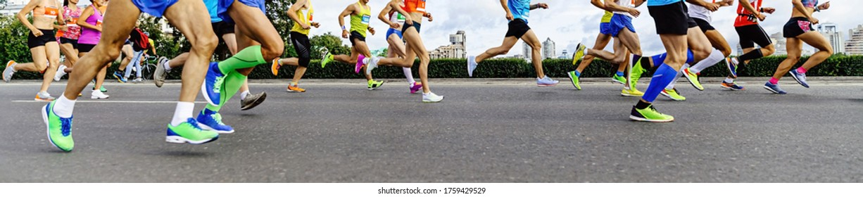 group athletes runners: men and women running city marathon in background of buildings