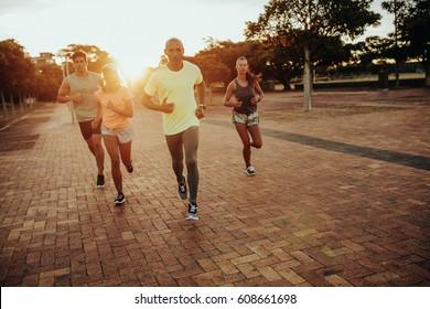 Group of athletes running at the city park. Runners in sportswear training together outdoors.