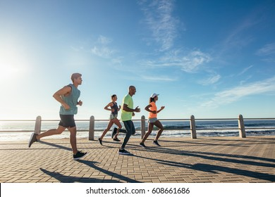 Group of athletes running on ocean front. Runners in sportswear training together outdoors.