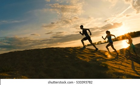 group of athletes - two girls and a guy are fleeing the mountain, near river at dusk