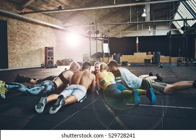 Group of athletic adults laying on their stomachs during pep or morale boosting session on floor at large cross-fit training gym