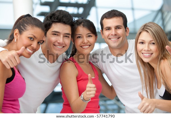 Group of athletic people at the gym with thumbs up