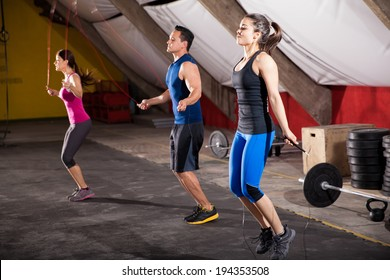 Group of athletic people using jump ropes for their workout in a cross-training gym