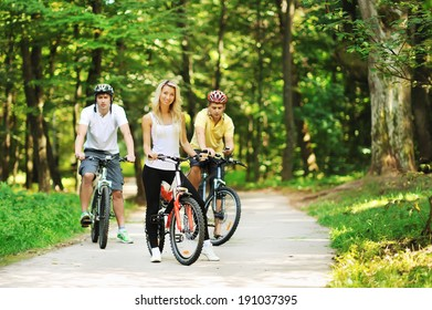 Group of attractive happy people on bicycles in the countryside