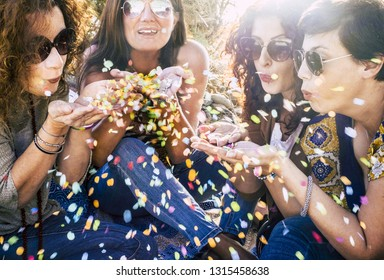 Group of attractive middle age young women playing and blowing out a lot of coloured confetti in the air - celebrate and having fun together with friendship - party outdoor concept with sun backlight