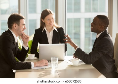 Group of attractive multiracial laughing businesspeople talking and joking sitting at desk in light modern office, friendly multi-ethnic business team having fun, discussing business issues at meeting