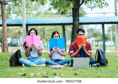 Group of attractive young people are tutoring exam with study book and laptop, sitting on the graden. Student group and tutoring education concept.
