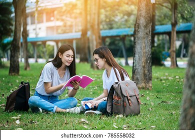 Group of attractive young people are tutoring exam with study book, sitting on the lawn. Student group and tutoring education concept., sitting on the lawn. Student group concept.