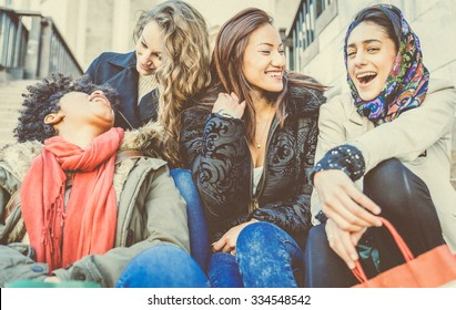 Group of attractive young women of different ethnics laughing and having party - Four students sitting outside university - Best friends spending time together