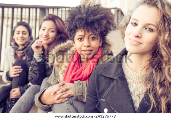 Group of attractive young women of different ethnics sitting on stairs and smiling at camera - Four students sitting outside university - Best friends spending time together
