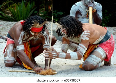 Group of Australian Aboriginals men demonstrating fire making craft during Aboriginal culture show in the far tropical north of Queensland, Australia.
