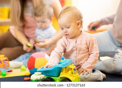Group of babies with mothers playing toys at playgroup