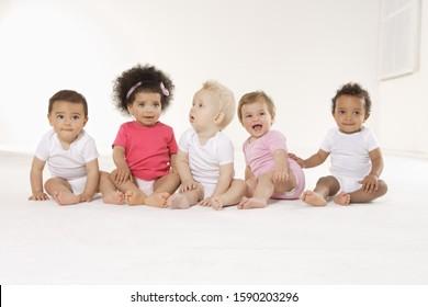 Group of babies sitting on floor