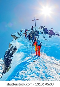 Group of back country skier ascending to the summit cross.