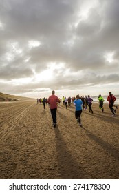 A group of back lit people in colorful outfits are running on a beach during the half marathon of Egmond.