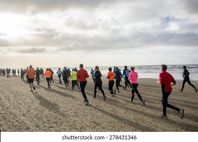 A group of back lit people in colorful outfits are running during a marathon that goes partly over a beach