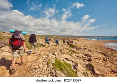 Group of backpackers walking on a sandy road along the sea shore on sunny sky background