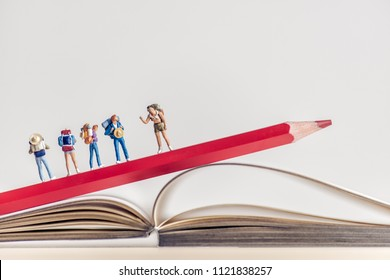 Group of backpackers walking over opened book. Travel concept