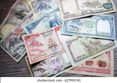 The group of banknotes of Nepalese rupee put on the dark brown table background, prepare money for travel at Nepal, Asia.