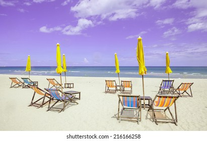 Group of beach chairs and closed umbrellas on white sand beach with cloudy sky. Concept for rest, relaxation, holiday.