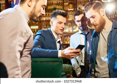 Group of bearded friends gathered together in pub after hard working day, chatting with each other and looking through photos on smartphone