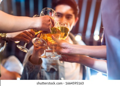 Group of beautiful Asian friendship people celebrating at rooftop party together, gang of best friend having cheerful drink and dance in music fun night lifestyle with light flare background