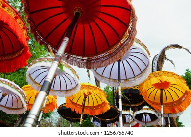 Group of beautiful Balinese flags and umbrellas at celebration ceremony in Hindu temple. Traditional design, arts festivals, culture of Bali island and Indonesia people. Indonesian travel background