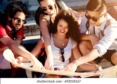 Group of beautiful best friends are together choosing a new destination on the map.