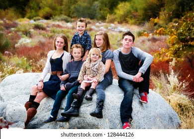 A group of beautiful children sitting on a rock with a Fall background